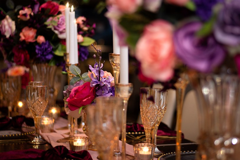 blackbird-wedding-reception-styling-amber-crystal-stemware-candlestick-holders-bright-faux-silk-flower-floral-arrangement-burbundy-velvet-napkins-blush-chiffon-table-runner