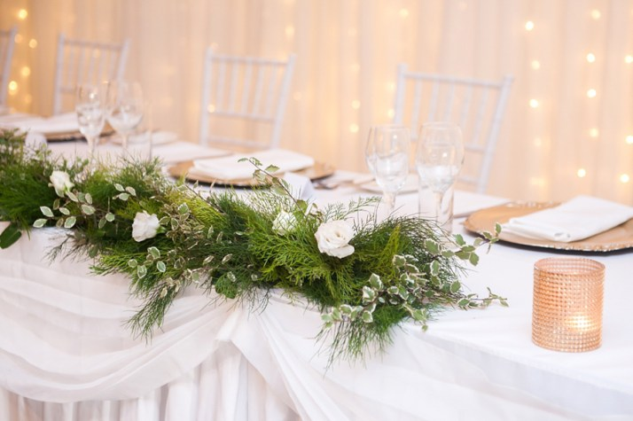 walkabout-creek-wedding-reception-styling-banksia-bridal-table-fresh-greenery-runner-candles-fairylight-backdrop
