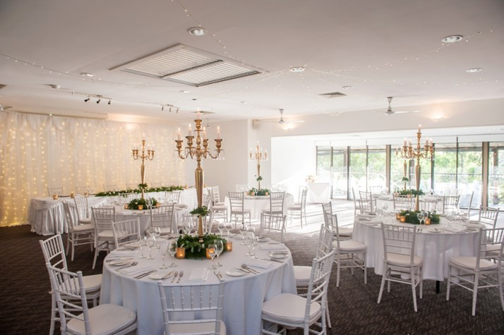 walkabout-creek-banksia-wedding-reception-styling-guest-table-gold-candelabra-greenery-centrepiece-faiylight-bridal-backdrop
