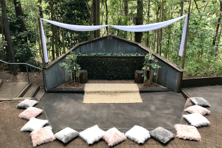 walkabout-creek-wedding-ceremony-styling-rainforest-white-draping-greenery-gold-stands-lanterns-woven-mat-rug-fluffy-cushions