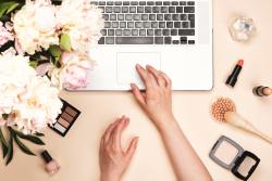 Beauty blogger workspace with laptop and cosmetics and peony flowers on pastel pink desk. Flat lay, top view