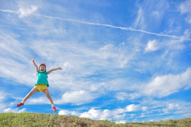 草原で子供がジャンプ