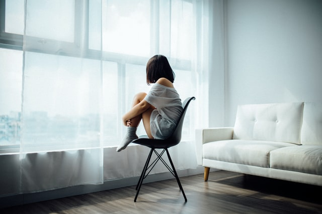 Girl sitting on chair looking out  of window