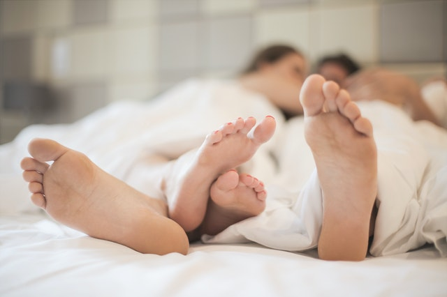 Image of feet of couple in bed