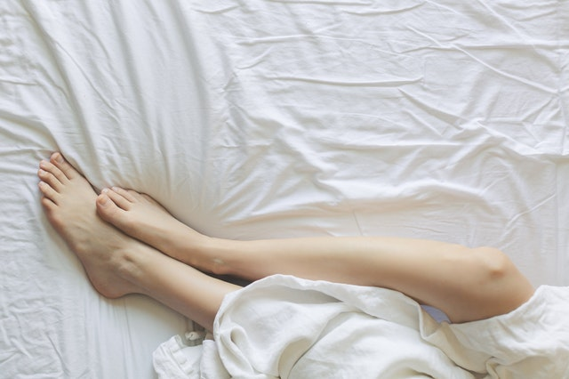 Woman legs wrapped in a bed sheet