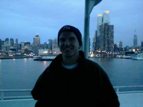 A cute guy in a NY Yankees knit cap at dusk with several lighted buildings behind him