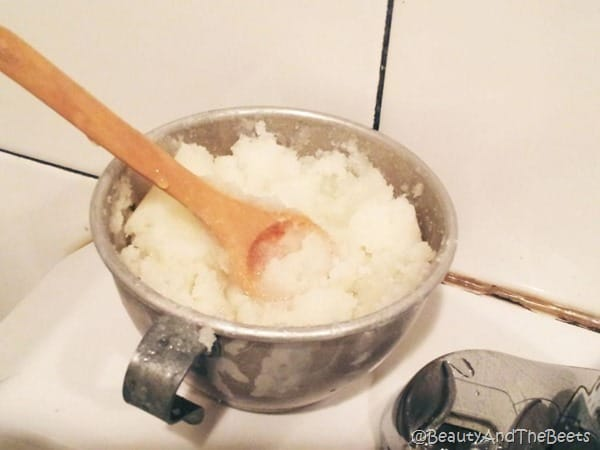 a silver cup filled with sugar scrub and a wooden spoon on a white counter with a white tile wall