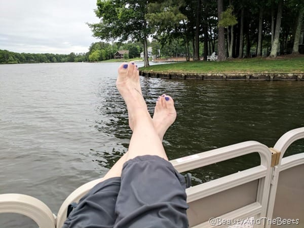 feet with pruple polish hab=nging over the side of a boat on a lake with lots of trees in the background