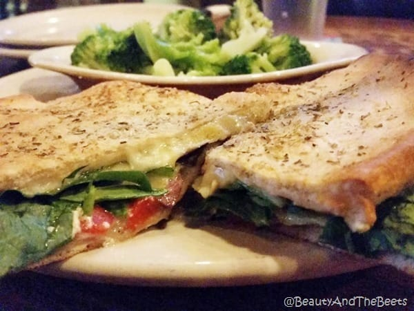 two wedges of a sandwich with a thin pizza crust with spinach, tomato, and cheese
