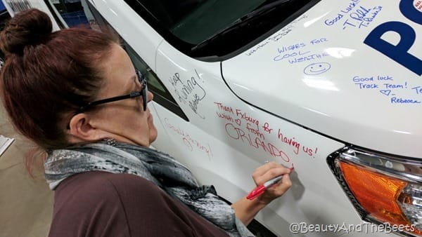 the author with a red sharpie writing on a white SUV