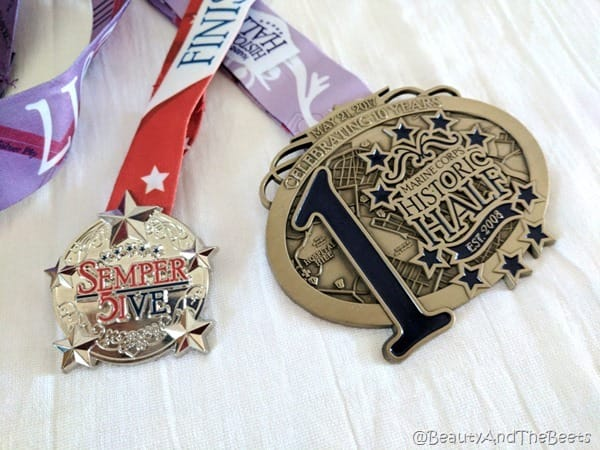 the Semper Five Miler medal and the much larger Historic Half medal on a white background