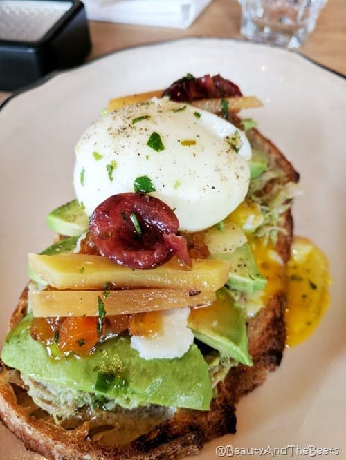 toast topped with avocado, cherries, squash, mangoes and a soft boiled egg on a white plate