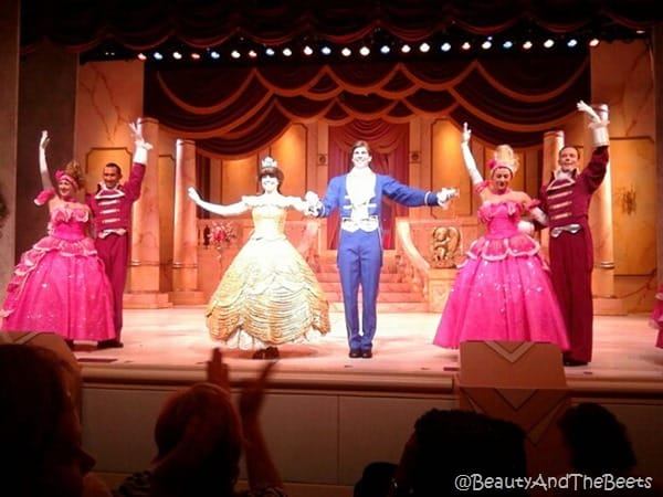 Belle in a gold ball gown, pink ball gowns, the Prince in a blue suit on stage