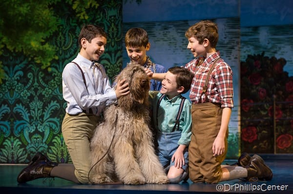 The four young boys in the cast of Finding Neverland surrounding the canine actor with a floral background