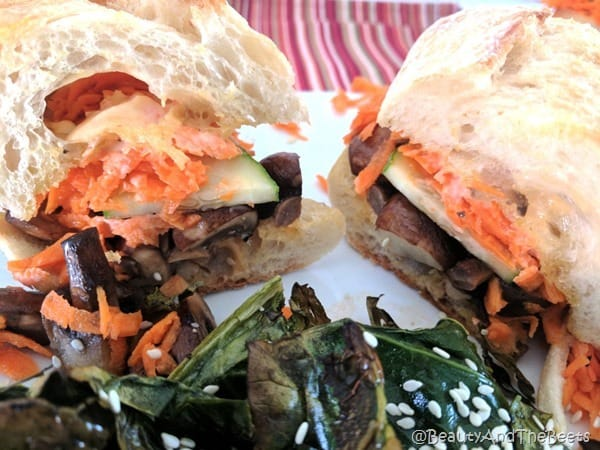 a colorful sandwich with shredded carrots and cucumbetrs on crusty bread with a serving a roasted greens in the foreground on a red striped placemat