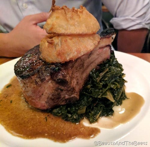 A large pork chop on collard greens on a white plate topped with onion rings