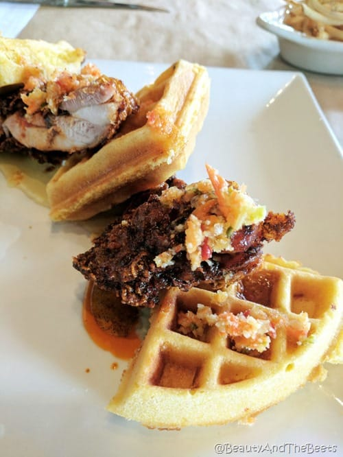 waffle wedges topped with golden fried chicken lined up on a white plate