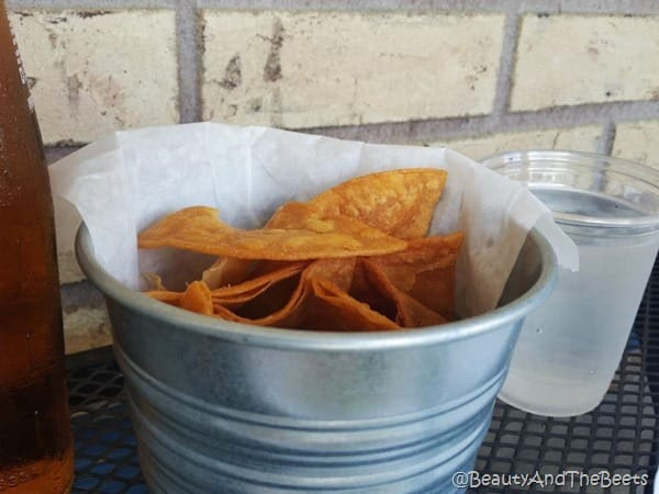 a silver bucket filled with tortilla chips on a black mesh table