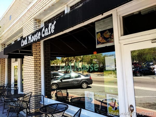 outside of the Cool Moose Cafe with white yellow brick and a large picture window a black awning