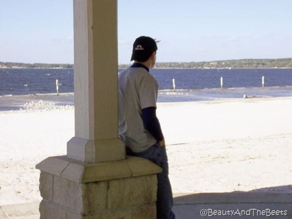 Mr Beet leaning on a pillar with his hat on backwards hands in his pockets looking out over a white sandy beach with Lake Minneola in the background