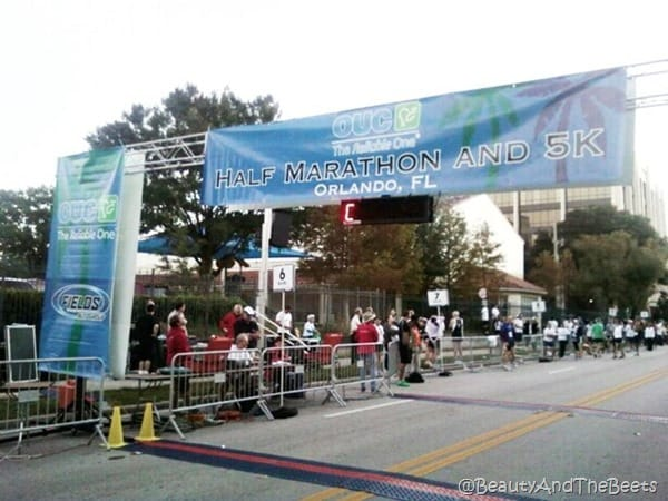blue banner of the finish line of the OUC Half Marathon in Orlando with a small crowd of people