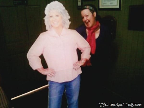 the author wearing a pink scarf next to a cutout of Paula Deen in a pink shirt