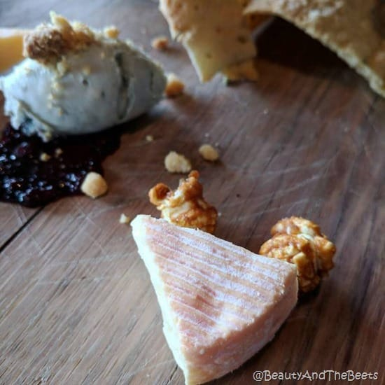a wedge of petite munster cheese garnished with caramel popcorn on a wooden table