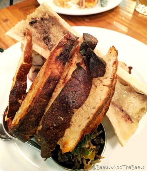 A white plate with a large half bone with marrow and bread neatly lined up on the bone