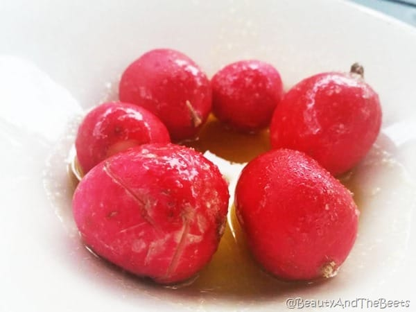 6 whole radish with olive oil drizzle and salt in a white bowl