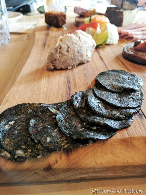 a pile of black salami with other meat on a wooden table