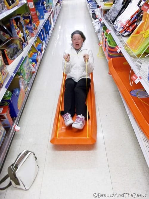 the author sledding in the middle of an aisle in a store on an orange sled screamming