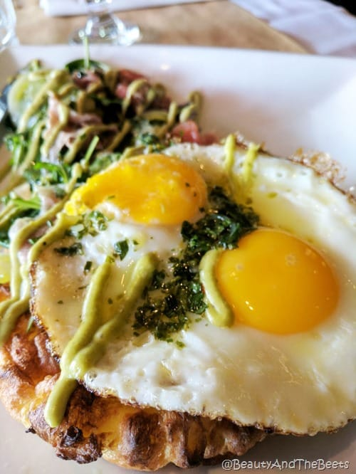 two fried eggs topped with pesto drizzle with a pile of greens and ham on a white plate