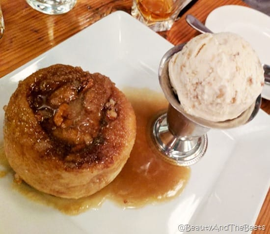 A large gooey sticky bun next to a scoop of butter pecan ice cream in a silver cup on a square white plate