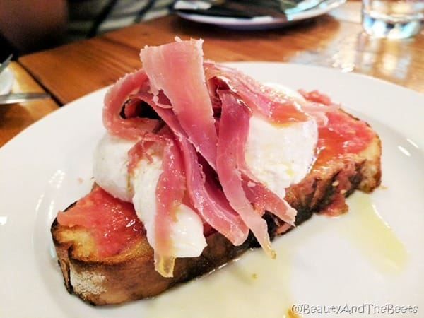 A piece of thick bread with tomatoes, a poachedd egg and sliced procuitto on a white plate