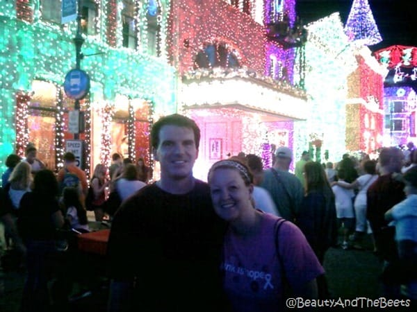 The author and Mr Beets pose in front of bright Christmas lights