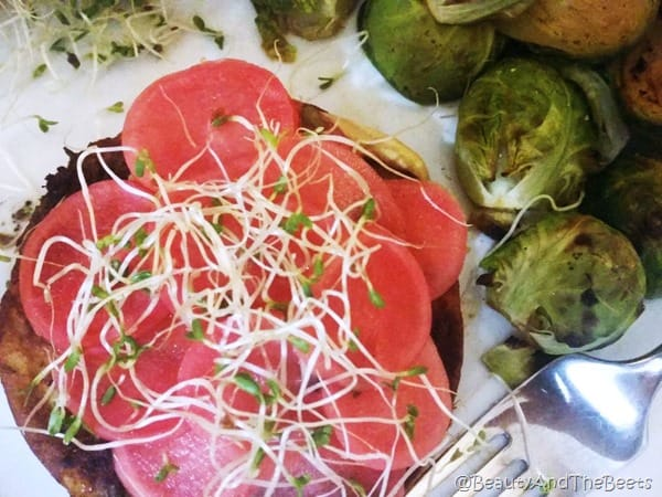 a veggie burger topped with bright pink pickled radish and a side of brussels sprouts on a white plate