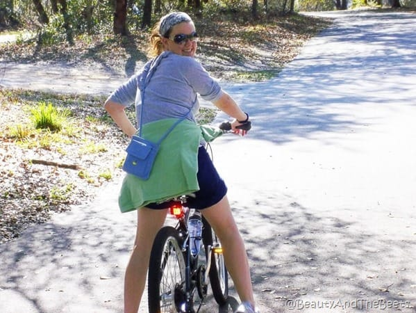 Anna on a bike with a green sweatshirt on a shaded and wooded trail looking back at the camera