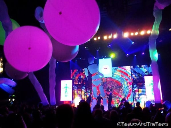 Blue Man Group in front of an abstract gaint picture with purple glow balls falling from the ceiling