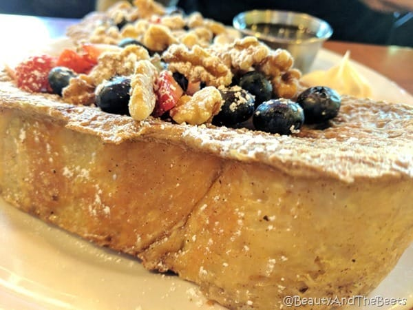 a super thick golden piece of bread with blueberries strawberries and walnuts on a white plate