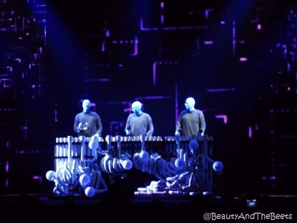 three Blue Man Group members in front of a giant xylaphone with a dark black background