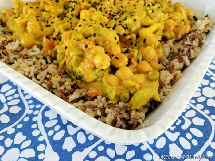 a white dish filled with a yellow curried vegetables and chickpeas with a sprinkling of black sesame seeds and brown grain rice in a white dish on a blue and white patterened placemat