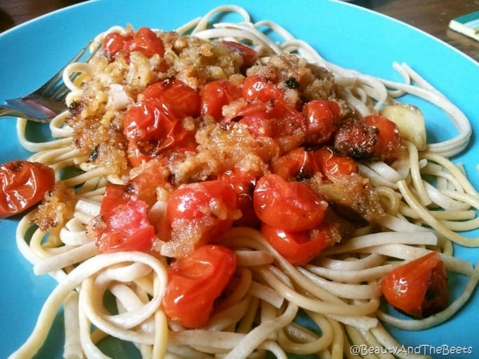 white linguine pasta topped with roasted tomatoes, garlic and breadcrumbs on a blue plate