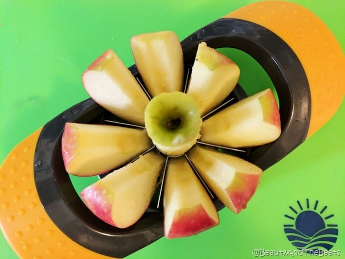 a red apple cut through an apple corer on a green background