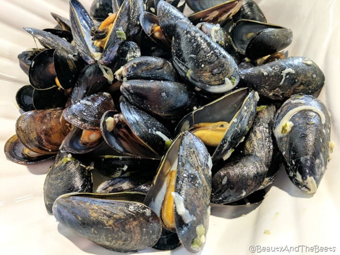 a pile of black mussels sprinkled with garlic in a white clam shell bowl