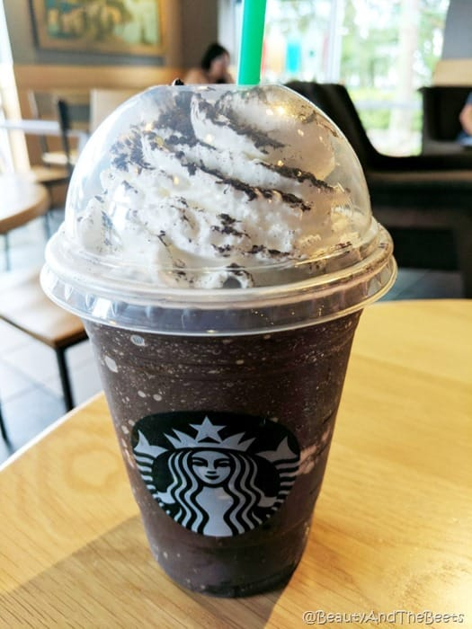 a dark chocolate frappuccino in a Starbucks cup on a light wooden table