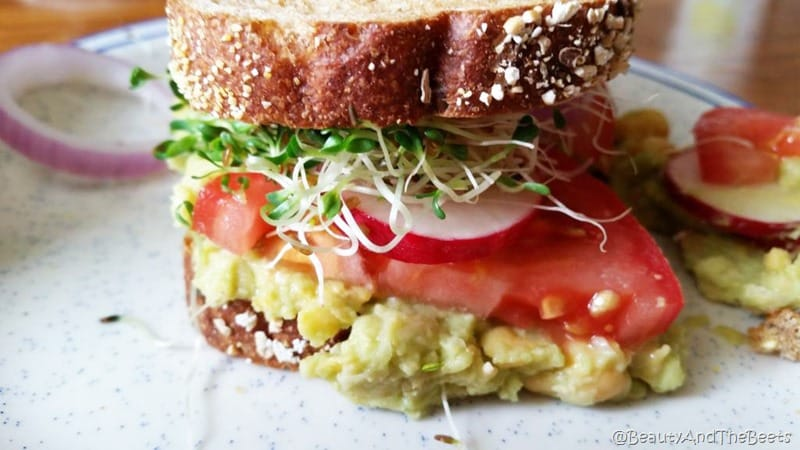 a colorful sandwich on wheat bread with red tomatoes, green alfalfa sprouts, hot pink radish and mashed chickpea and avocado on a white plate