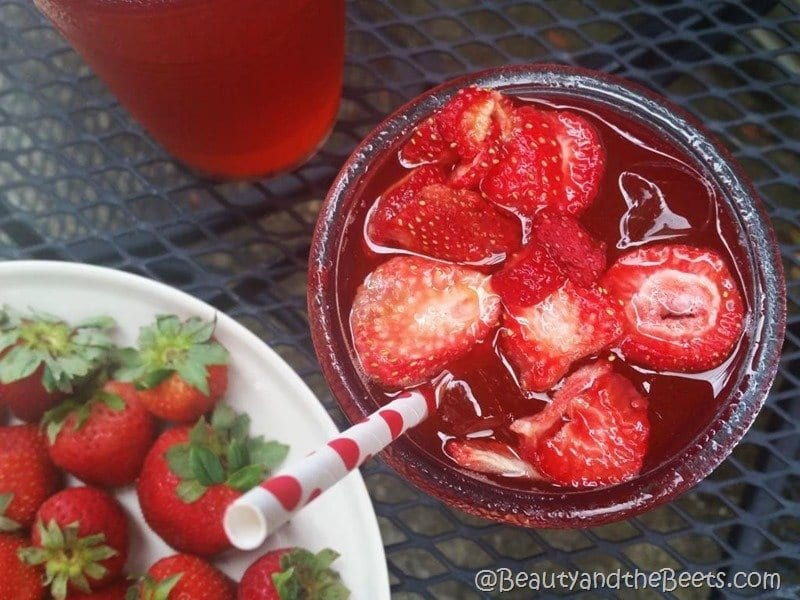 An overhead shot of a red iced drink with a red and white polka dot straw on an outdoor table with a white plate of fresh red strawberries