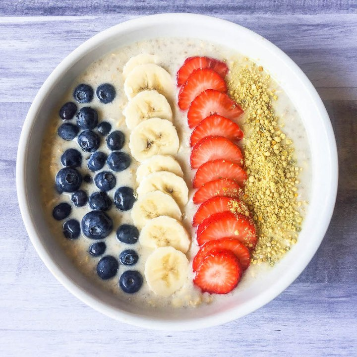 overnight oats in a bowl with strawberries, bananas, blueberries and bee pollen