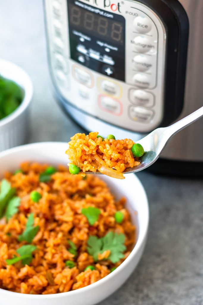 a forkful of prepared Spanish rice with an instant pot in the background