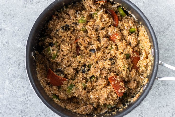 quinoa in a pot mixed with cheese, pepperoni, green pepper and olives